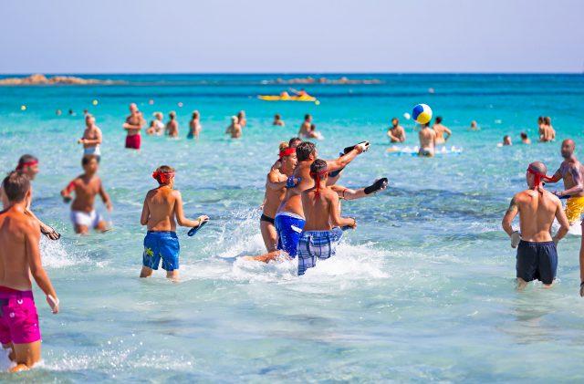 Jungen, die Spaß im Meer am Strand von Camping Cala Ginepro haben