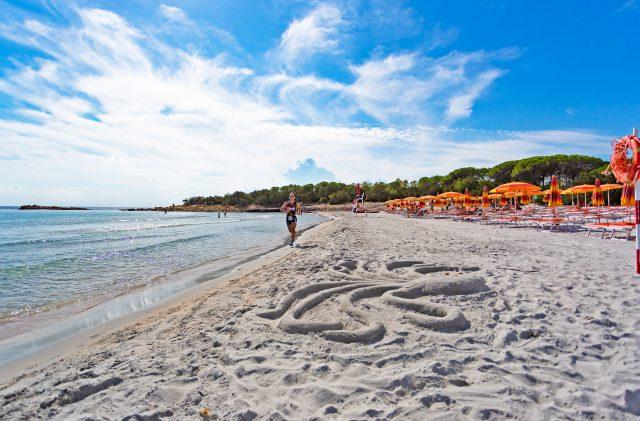 Runner che corre sulla riva, nella spiaggia Cala Ginepro in Sardegna